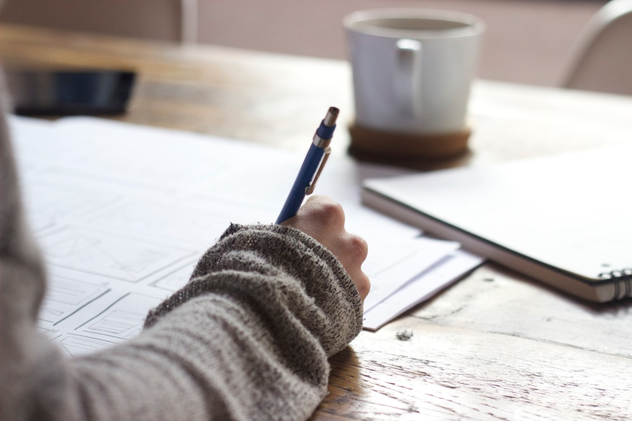 A person writing with a cup in the background
